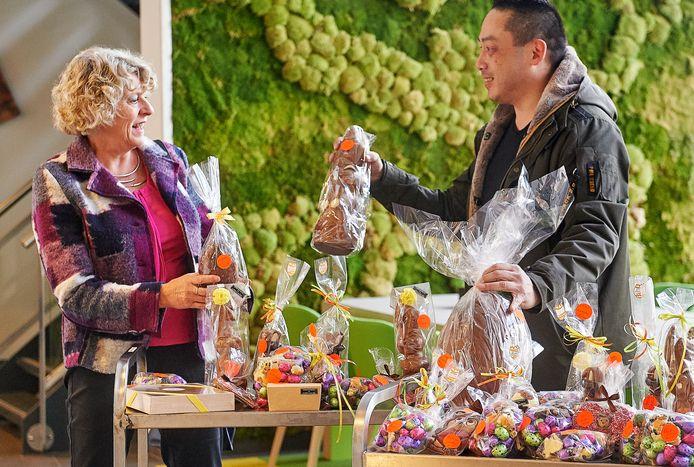 Sjo-Wah Lain geeft alle chocoladeproducten die hij voor Pasen heeft ingeslagen aan zorgmedewerkers. Wilma de Jong (links) neemt het in ontvangst.