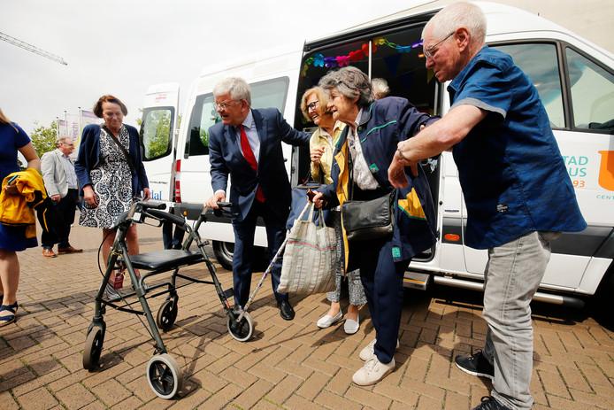 Burgemeester Jan van Zanen helpt senioren een handje bij de PlusBus.