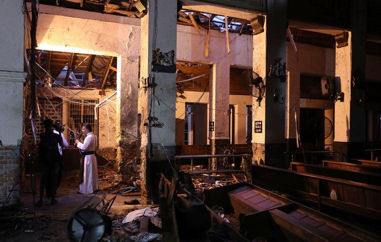 Een katholieke priester praat tegen de media in de beschadigde St. Anthony's kerk in Colombo, Sri Lanka. Beeld AP