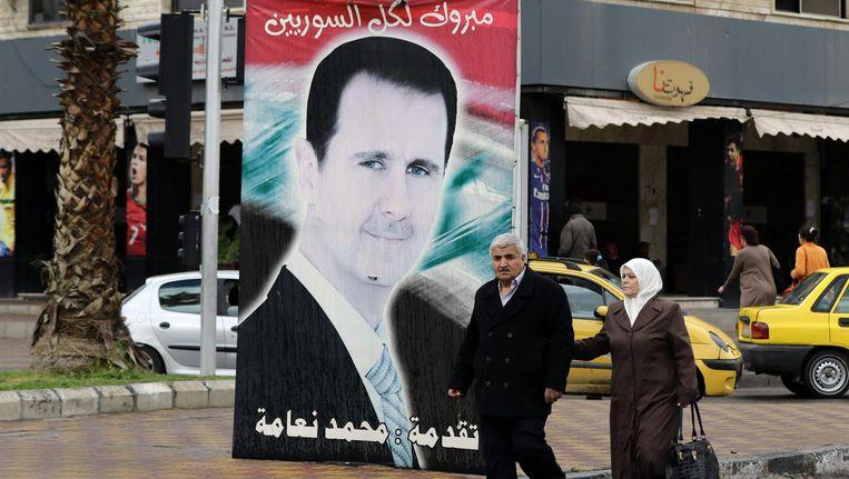 Een groot portret van Basher al-Assad in de Syrische hoofdstad Damascus. Beeld afp
