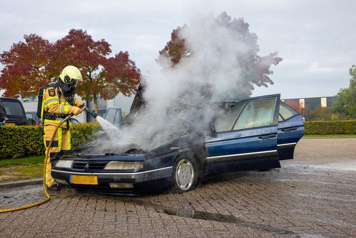 Een brandweerman blust de brandende auto.