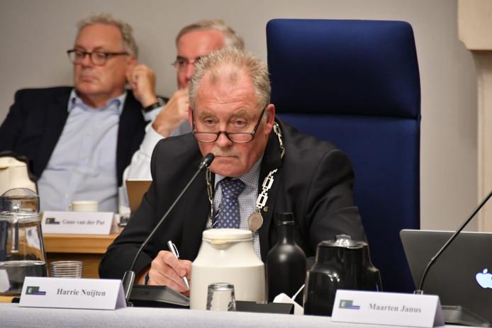 Waarnemend burgemeester Harrie Nuijten tijdens de raadsvergadering in Hilvarenbeek donderdagavond. Links achter hem wethouders Gerrit Overmans (l) en Guus van der Put.