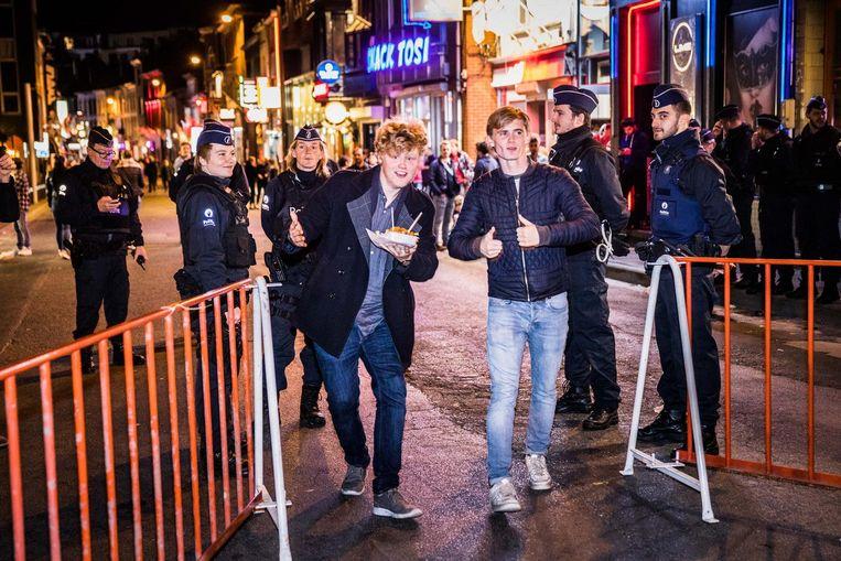 De politieagenten laten twee feestende studenten door aan de controlepost.