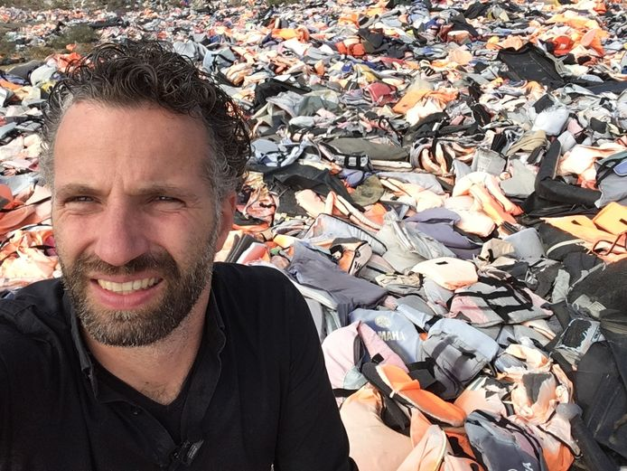 Jurrien ten Brinke met op de achtergrond een zee aan reddingsvesten op het Griekse eiland Lesbos.