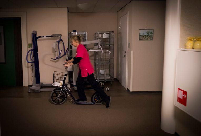 Een verpleegkundige verplaatst zich tijdens haar nachtdienst per step. Beeld Martijn Beekman / de Volkskrant