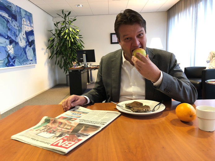 Burgemeester Van Midden (Roosendaal) neemt een hap van zijn appel.