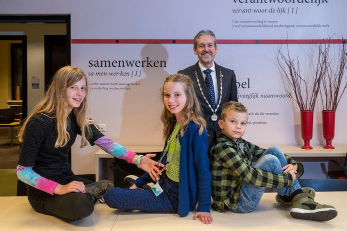 Mila Petersen (midden) vergezeld van haar zusje Suze en haar broertje Noud, met op de achtergrond de 'burgemeester voor grote mensen' Hans van der Pas.