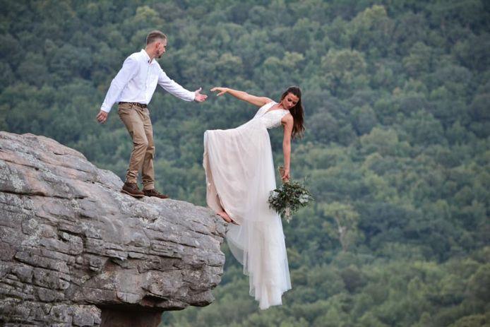 Ils posent sur le bord d'une falaise pour leur séance de photos de mariage.