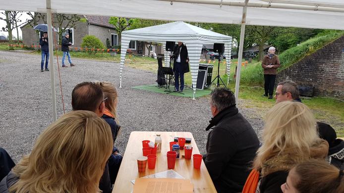 Wethouder Schlösser spreekt van onder een tent de aanwezigen toe.