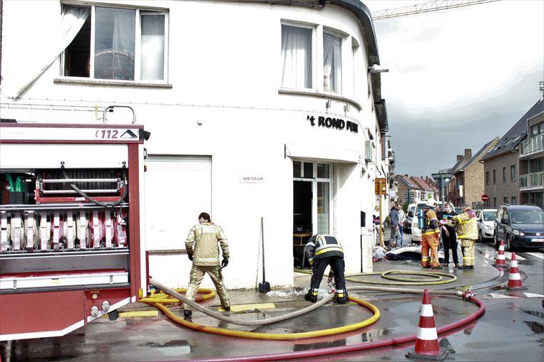 De brandweer aan het café. Het vuur ontstond in een appartement boven de zaak.