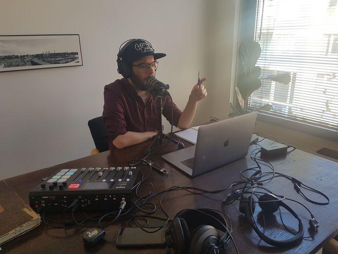 Kevin Goes thuis bezig met zijn podcast Achter het Verhaal