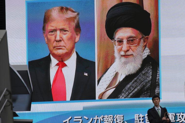 Een man in Japan loopt langs een billboard met daarop het laatste nieuws over de spanningen tussen de VS en Iran. De hoogste leider van Iran, Ali Khamenei, en de Amerikaanse president Donald Trump staan lijnrecht tegenover elkaar.  Beeld AP