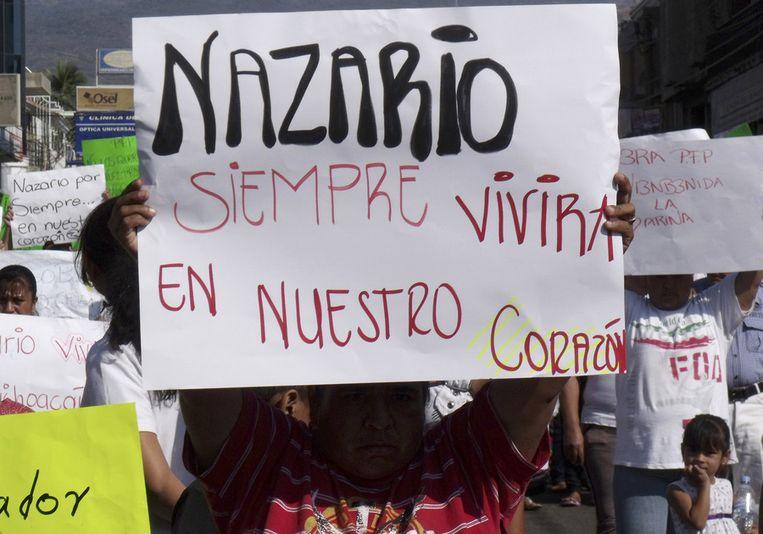 Een Mexicaan houdt een bord omhoog waarop staat: 'Nazario zal altijd voortleven in ons hart'. De foto dateert van 12 december 2010, kort na de eerste berichten over de dood van de drugsbaas. Beeld ap