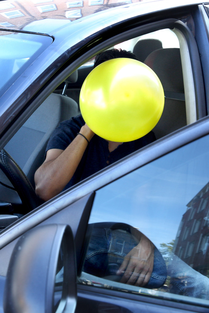 Een jongen die lachgas in de auto gebruikt. Foto ter illustratie.