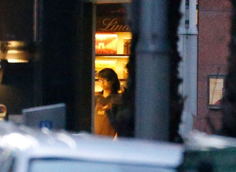 Een van de gegijzelden is te zien door de ramen van het Lindt café. Volgens Australische media doet de vrouw het licht van het café uit. Beeld reuters