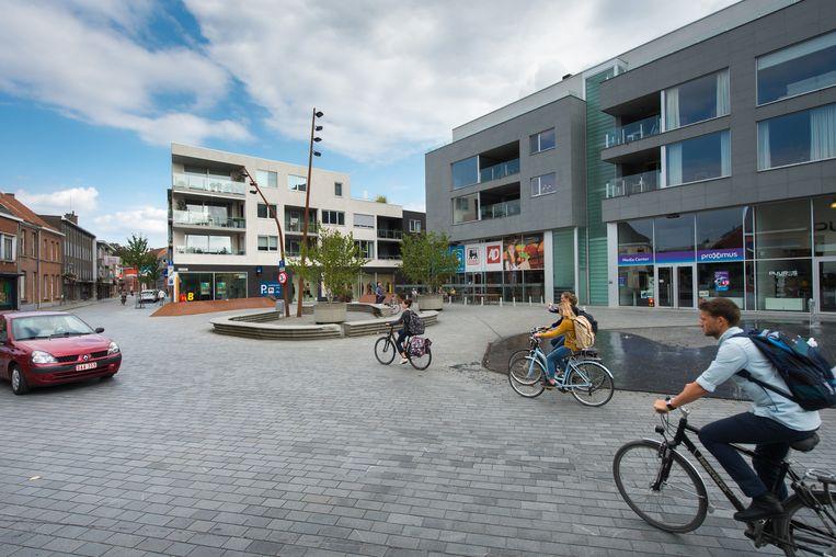 Een auto en een fietser rijden schijnbaar op dezelfde rijbaan. Op het hele plein zijn er geen wegmarkeringen aangebracht.