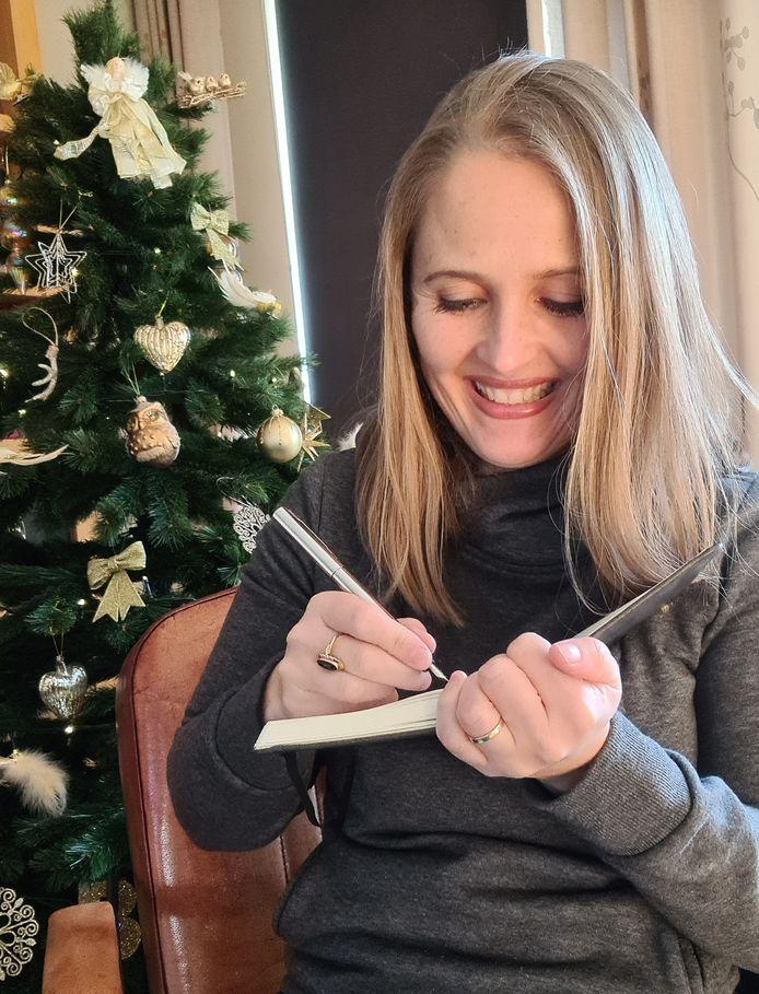 Saskia schrijvend bij de kerstboom.