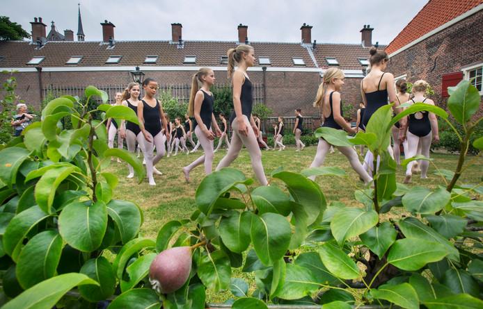 De danseresjes van balletschool Elsa Vreeken luisteren op Oranjeappeldag op tijdens de openstelling van de Hof van Wouw aan de Lange Beestenmarkt.