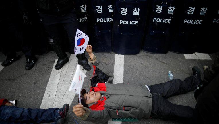 Een aanhanger van de afgezette Zuid-Koreaanse president ligt uit protest voor oproerpolitie in Seoul. Beeld reuters