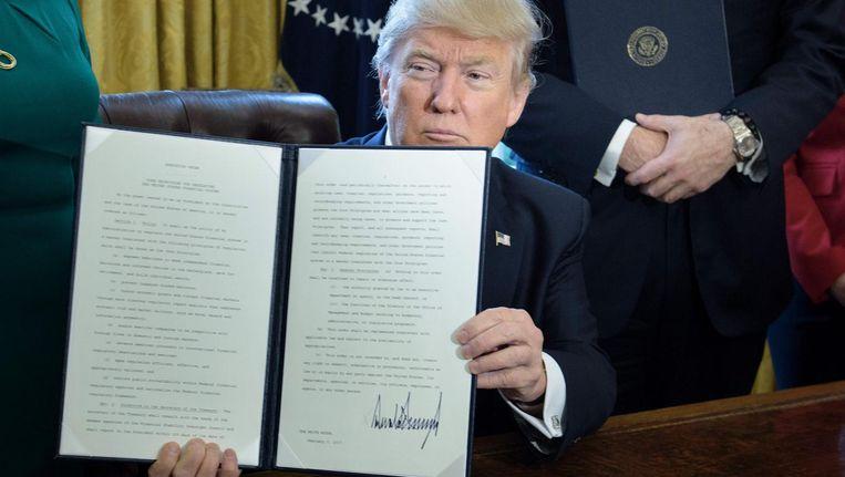 President Donald Trump toont het vers ondertekende decreet waarmee de 'Dodd-Frank act' moet worden herzien. Beeld afp