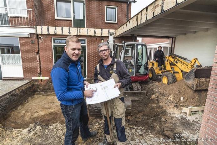 Martijn Borgerink van aannemersbedrijf Oude Moleman (links) en Peter ter Haar, eigenaar van de woning, bekijken de tekening van de uitbreiding. Rechts op de shovel Bart Leferink.