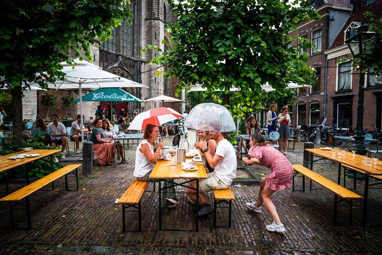 Jongeren drinken vrijdagavond in de regen een drankje onder een paraplu op het terras van café De Uyl van Hoogland in Leiden.  Beeld Freek van den Bergh
