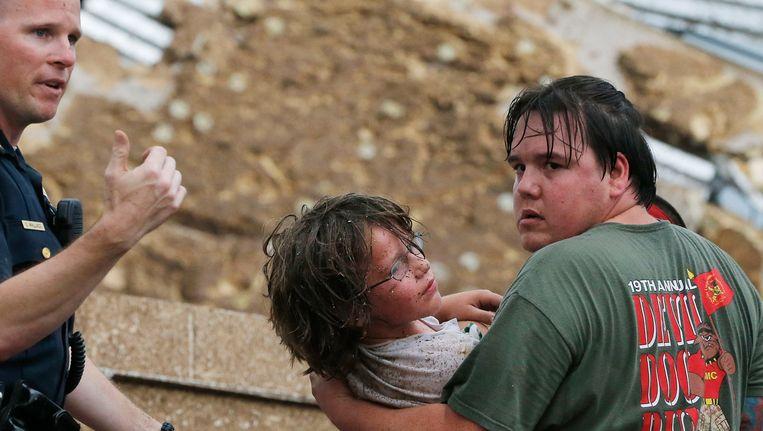 Een kind wordt weggehaald bij de ingestorte basisschool Plaza Towers. Beeld AP