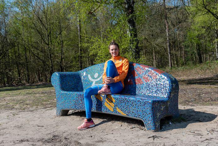 Hardloopster Julia van Velthoven bij het 'Warandeloop-bankje' in de Oude Warande.