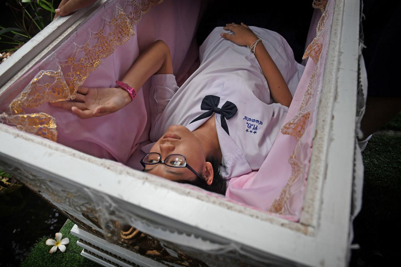 Een Thais meisje probeert hoe een traditionele lijkkist ligt, in het Kid Mai Death Awareness Café, een ontmoetingsruimte in Bangkok, waar het publiek wordt geïnformeerd over het boeddhisme en de dood. Foto Lillian Suwanrumpha