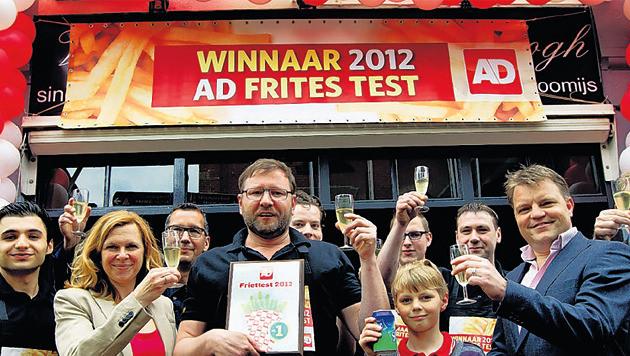 Arn Zuyderduin, op de foto hierboven geflankeerd door vrouw en zoon, heft het glas op de uitverkiezing tot beste patatbakker.