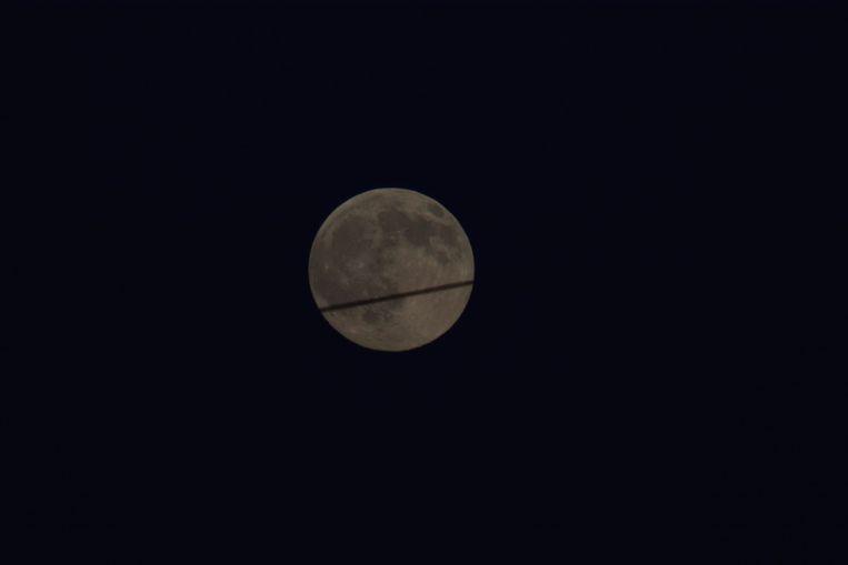 Op dit beeld zie je de maan met op de voorgrond een condensspoor van een vliegtuig.