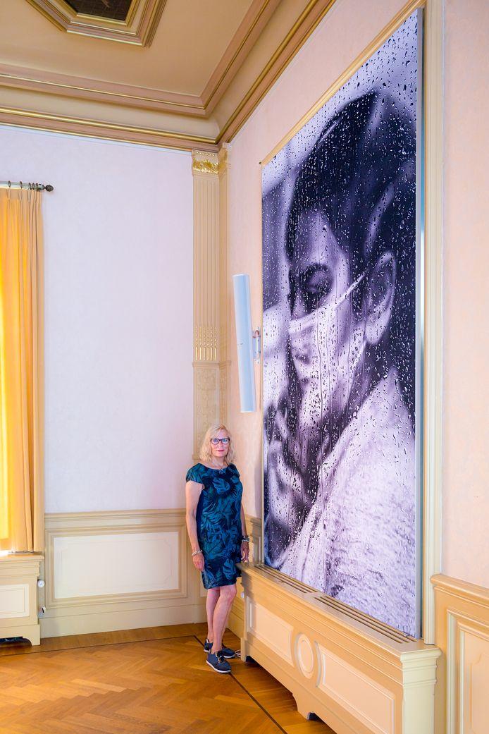De Zoetermeerse fotograaf Annelize van der Helm bij het metersgrote doek met haar foto in het Hilversum Museum.