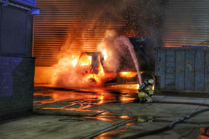 Een brandweerman blust de vlammende vrachtwagen.