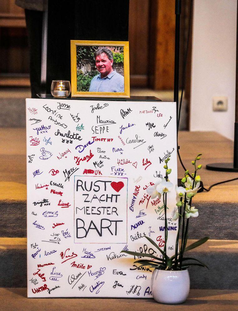 Vooraan de kerk prijken het bord 'Rust zacht, meester Bart' en een kleurrijk werkje van de leerlingen.