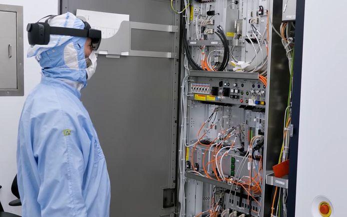 Een monteur van ASML bekijkt een systeem van een chipmachine, waarbij een specialist op afstand meekijkt.