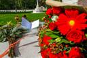 Bloemen bij het  Oorlogsbegraafplaats in Mierlo na dat het beklad werd met hakenkruis op kapel en leuzen op monument en graven.