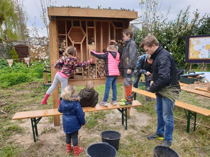 Jonge Hankenaren vullen het insectenhotel met natuurlijke materialen.