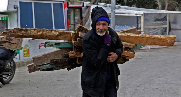 Een Afghaanse man sleept brandhout aan in het Karatepe vluchtelingenkamp op Lesbos.