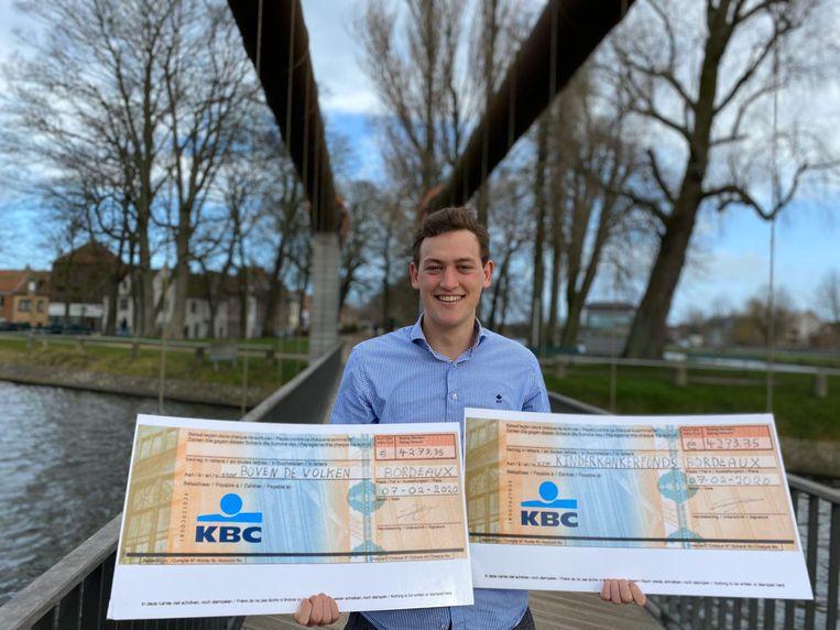 Hendrik met twee symbolische cheques voor het Kinderkankerfonds en vzw Boven De Wolken.