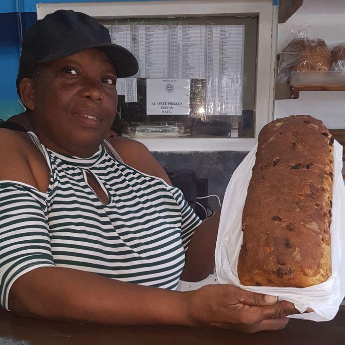 De eerste Curacaose krentenwegge. Adelheid Hous, medewerkster van bakkerij De Zon, showt hem met trots