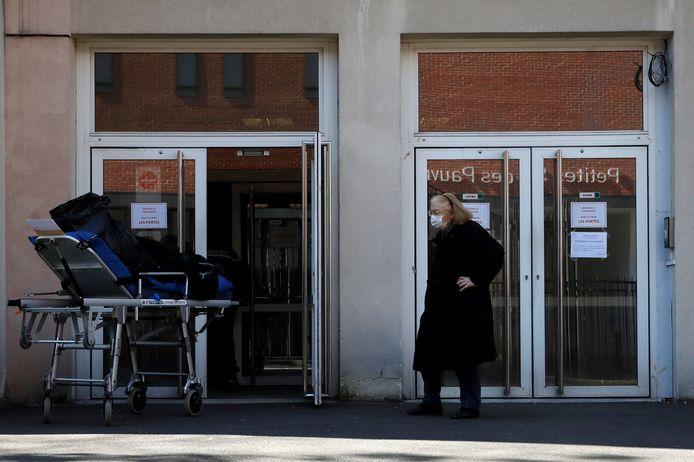 Een Franse vrouw voor een bejaardenhuis, waar onlangs 16 bewoners overleden  door het coronavirus en 81 besmet raakten.