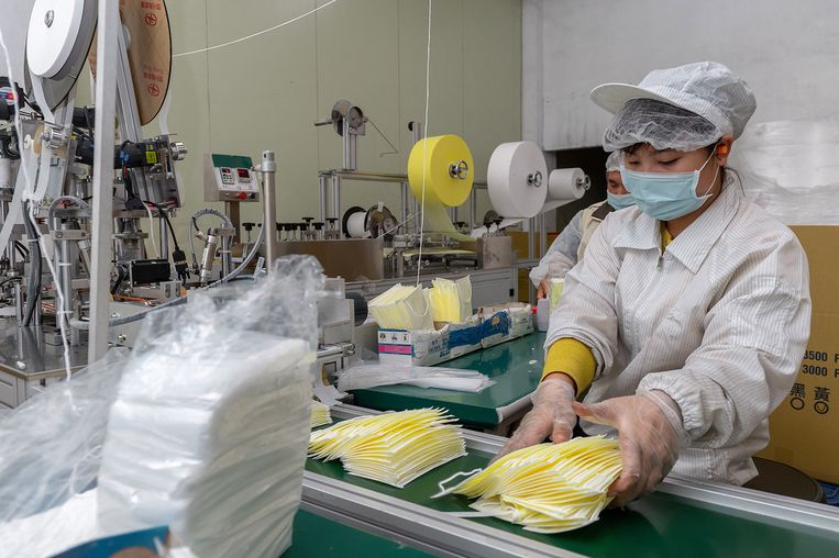 Een werknemer met een masker in een fabriek in Taiwan. Beeld EPA