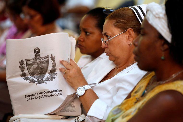 Een Cubaanse verpleegkundige bekijkt de conceptgrondwet bij een bijeenkomst in een kliniek in Havana, 13 augustus. Beeld Reuters