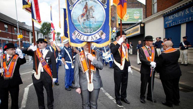 Leden van de Oranjeorde staan woensdag klaar voor hun mars door de straten van Belfast. Met de Oranjemarsen vieren Noord-Ierse protestanten jaarlijks op 12 juli dat Willem III bij de slag om de Boyne in 1690 zijn katholieke schoonvader James II versloeg. Beeld null