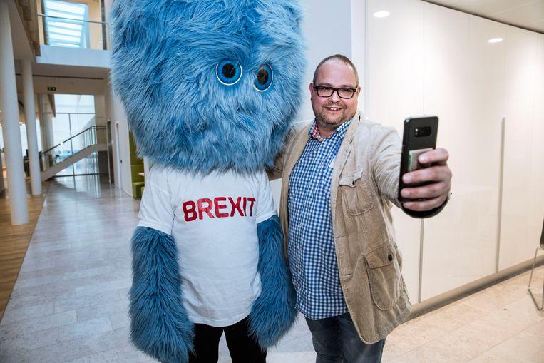Ondernemer Arjen Hes maakt een selfie met het brexit monster. Beeld Arie Kievit