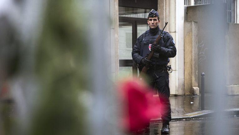 Een agent houdt de wacht voor het redactiekantoor van Charlie Hebdo. Beeld epa