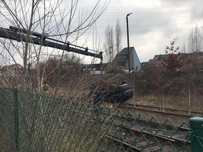 De auto belandde op de treinsporen.