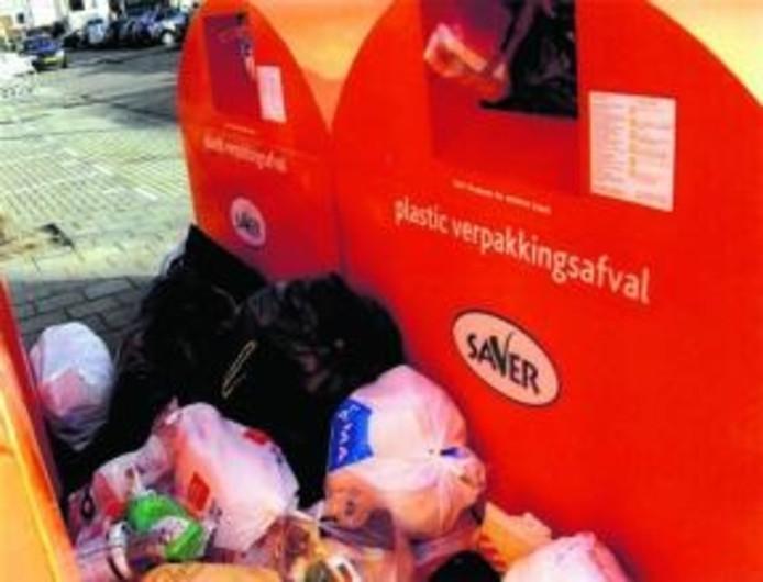 Een grote rommel bij een bak voor plastic huishoudelijk afval. Mensen zetten hun spullen ernaast omdat de container overvol is. foto Lijst Linssen