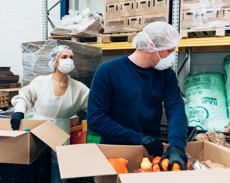 Freke van Nimwegen (achter) bij het inpakken van de boodschappenpakketten bij het Food Rescue Center Instock in Amsterdam. Beeld Rebecca Fertinel