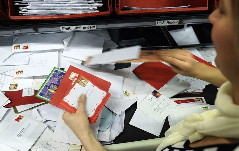 Een postsorteerder sorteert kerstkaarten. Beeld ANP